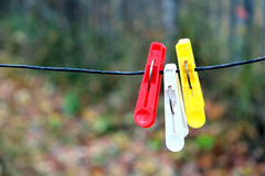 Three clothespins hanging on a rope Royalty Free Stock Photo