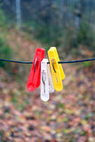 Three clothespins hanging on a rope Stock Photo