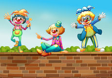 Three clowns above the wall Stock Photo