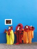 Three clowns performing. Three white clowns in the yellow, red, and orange traditional theatrical clown's costumes are performing in front of blue wall with Stock Photography