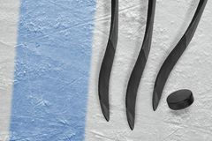 Three hockey sticks, a puck and a fragment of the ice arena with. Three clubs, a washer, a blue line and the background of the hockey arena. Concept, hockey stock photo