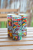 Three Coca Cola cans. Woodstock edition on a wooden table Royalty Free Stock Image