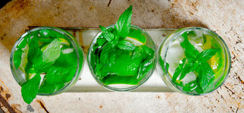 Three cocktail glasses with ice cubes, lime, mint leaves and rum . On the old background. Royalty Free Stock Images