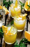 Three cocktails from fresh oranges with ice and mint leaves on wooden background Stock Photo