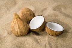 Three coconuts on the sand. 3 coconuts over the sand, one split in half Royalty Free Stock Image