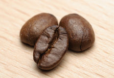 Three Coffe beans. Three Coffee beans on a wooden surface Stock Photo