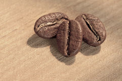 Three coffee bean with sunlight. On wooden plate Royalty Free Stock Images