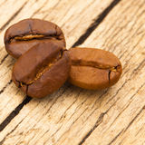 Three coffee beans on old table - close up shot Royalty Free Stock Photography