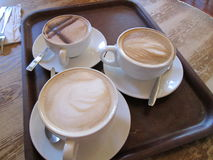 Three Coffee beverages on a tray. In mugs on a table Royalty Free Stock Photo