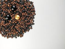Three coffee capsules surrounded by coffee beans with blank space..Top view. Three coffee capsules surrounded by coffee beans with blank space. Top view royalty free stock images