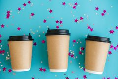 Three coffee cardboard craft cups lie on blue background with confetti. Mock-up. Top view. Flat lay. stock photography