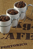 Three coffee cups. On the background burlap Stock Photography