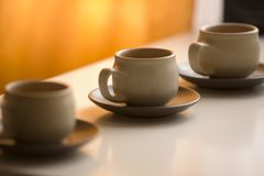 Three coffee cups and saucers. A view of a set of three ceramic coffee cups and saucers setting on a table or counter top Royalty Free Stock Photography