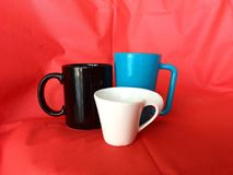 Three coffee or tea cups with red fabric background royalty free stock photo