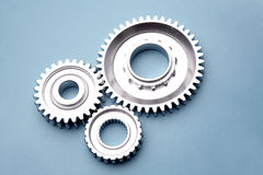 Three cogs. On blue background Stock Photos