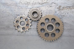 Three Cogs. A group of solid metal gears are linked together on a grungy steel background. This set of industrial cog wheels can be used to represent the concept Royalty Free Stock Photo