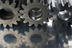 Three cogs in a row. Cogs, gears reflection in stainless-steel Stock Photos