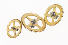 Three cogwheels. Three old gold-coloured little cogwheels are connected Stock Photography