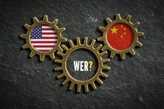 Three cogwheels with the flags of USA and the China and the word `Who?` in German in the middle. Three cogwheels on slate background with the flags of USA and royalty free stock photo