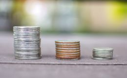 Three coins stack on the wooden table with bokeh garden blurred background Stock Photo