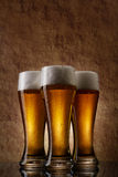 Three cold Beer into glass on a old stone Royalty Free Stock Images