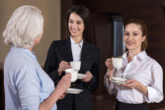 Three colleagues communicating during coffee break at workplace Royalty Free Stock Photography