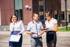 Three colleagues discussing work in an innovative town. Consider graphics,businesswoman talking on the phone Stock Photo