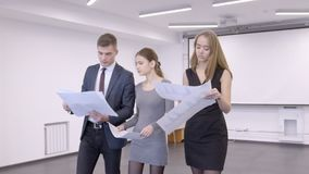 Three colleagues are going throug the conference room in their office. Businessman in dark blue suit and red tie and two female managers in grey and black stock video footage