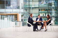 Three colleagues at a meeting in the foyer of a big business Stock Images