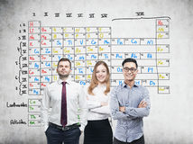 Three colleagues and periodic table Stock Image