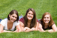 Three College Friends. Laying Down in Grass royalty free stock photo