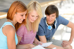 Three college friends studying looking into book Royalty Free Stock Photo