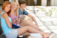 Three college student friends with tablet smiling Stock Photos