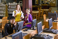 Three college students hanging out in library. Two pretty female university students with male student using computer in library Royalty Free Stock Image