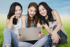 Three college students with laptop at field. Beautiful teenage girls sitting on the meadow while using a laptop computer together Stock Images