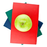 Three color books and green apple view from top. On white background stock images