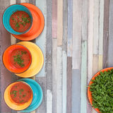 Three color bowls with tomato gazpacho soup and a red plate with Royalty Free Stock Photos