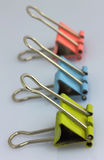Three color clips for papers. Are on a gray table Royalty Free Stock Photos