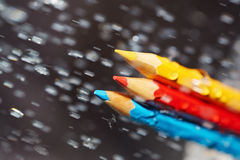 Three color pencils under the rain Royalty Free Stock Image