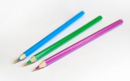 Three color pencils on white background. Three color pencils (blue, green, magenta) on a white background; focused on middle pencil tip Stock Photos