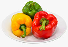 Three color peppers isolated on white. The three colored peppers on the plate Stock Photo