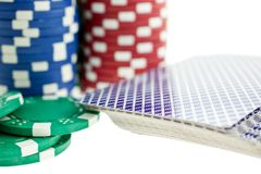 Three color poker chip stacks and cards deck Stock Photography