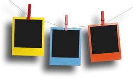 Three color polaroid photos hanging Royalty Free Stock Photos