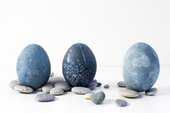 Three colored blue, gray marble eggs stand vertically among the stones stock photography