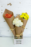 Three colored bouquet of carnations in paper cornet royalty free stock photo