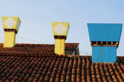Three colored chimneys in Burano in the municipality of Venice in Italy Stock Photography