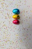 Three colored chocolate easter eggs on white background and colorful confetti royalty free stock images