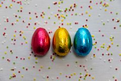 Three colored chocolate easter eggs on white background and colorful confetti stock photo