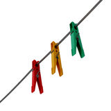 Three colored clothespins. Three clothespins red, yellow and green colors, hanging on a cord isolated on a white background Stock Photography