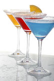 Three colored cocktails 3. A close up view of martini glass with different colored cocktails and a piece of orange Royalty Free Stock Photos
